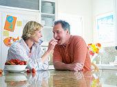 Woman feeding man strawberry in kitchen, smiling